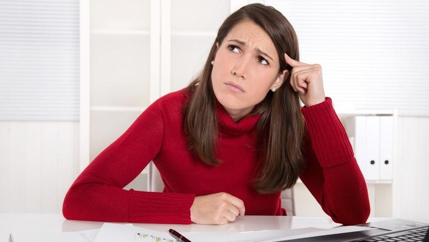 Buchführung: Junge Frau denkt über ihre BWA - Betriebswirtschaftliche Auswertung - nach