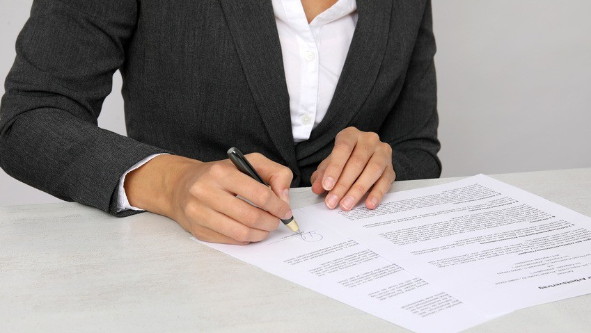 Junge Frau unterzeichnet Arbeitsvertrag