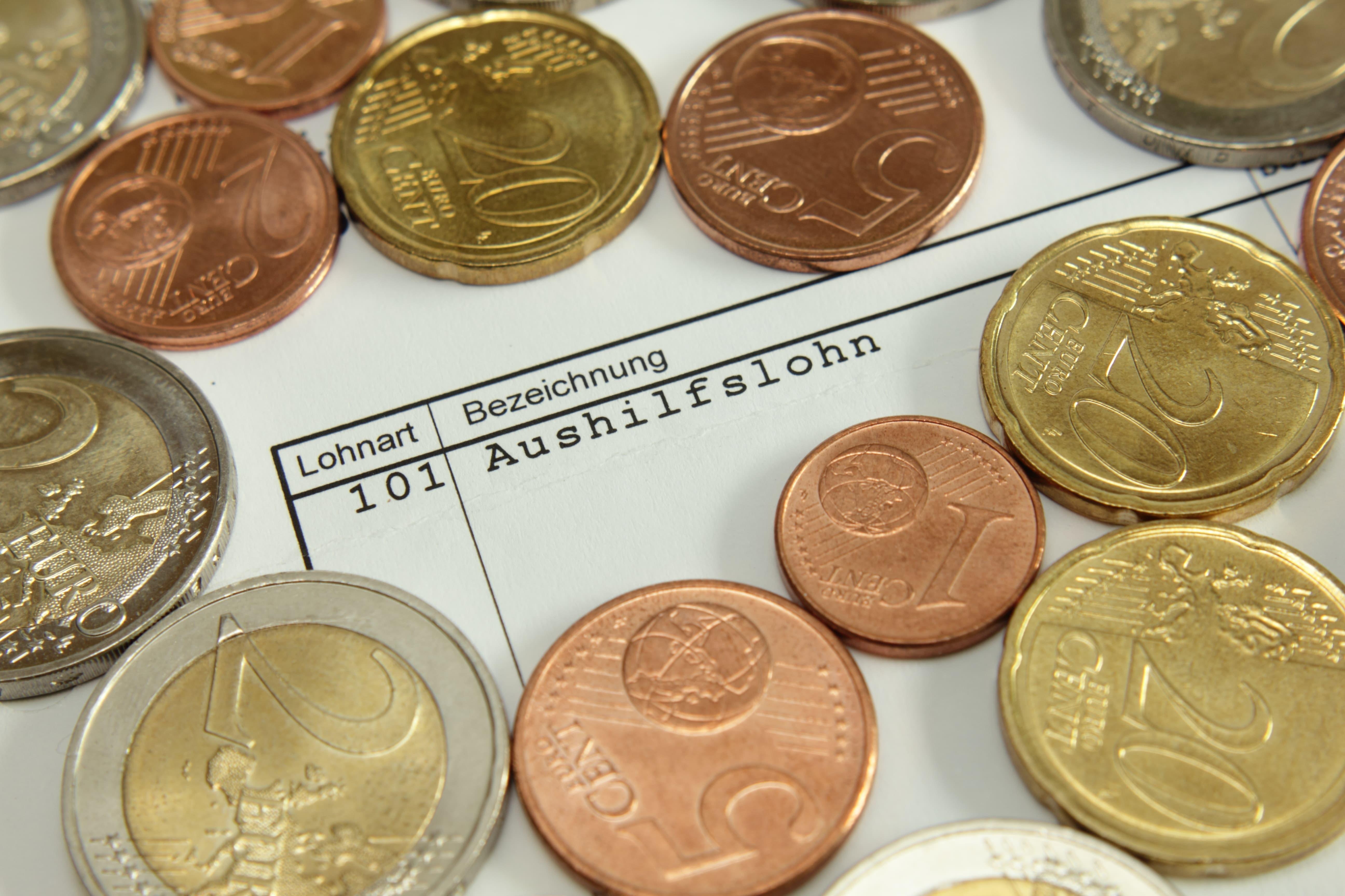 Münzgeld und Gehaltsabrechnung einer Aushilfe